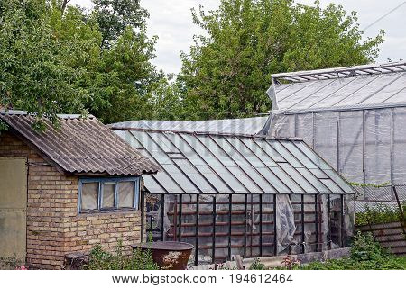Brick barn and greenhouses in the yard on a plot in the garden