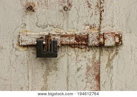 Large iron padlock on the bolt on the metal door