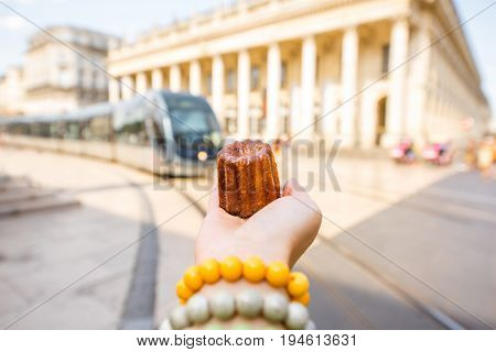 Holding a traditional Bordeaux sweet cake called Canele outdoors on the street near the Grand theatre building in Bordeaux