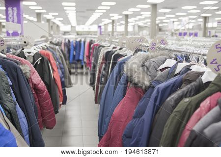 Men's jackets and down jackets on a hanger on the counter in the store