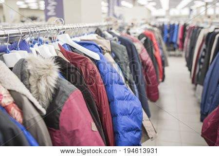 Men's jackets and down jackets on the counter in the store