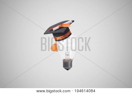 light bulb with graduation hat on gray background. concept education of new idea with innovation and creativity.