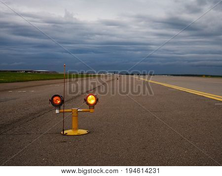 Yellow lantern on the runway against the rainy sky background