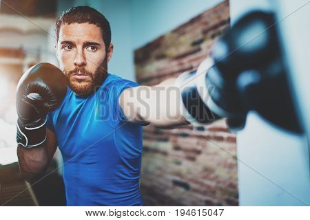 Young man athlete boxing workout in fitness gym on blurred background.Athletic man training hard.Kick boxing concept.Horizontal