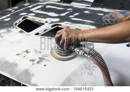 Auto body repair series: Closeup of mechanic sanding car bonnet