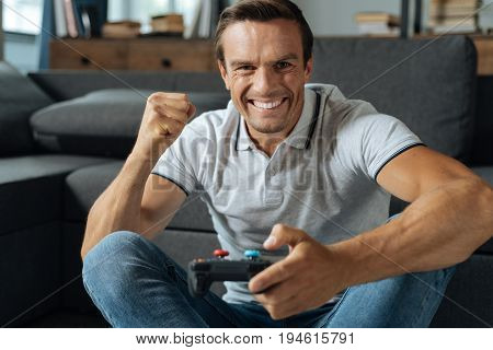 Home champion. Energetic ambitious enthusiastic man spending his weekend at home and enjoying his hobby while completing the mission of the video game