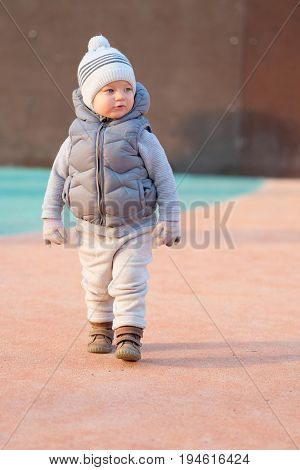 Portrait of toddler child in warm vest jacket outdoors. One year old baby boy wearing vest jacket at playground during sunset.
