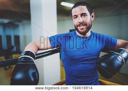Young smiling kick boxing man ready to muay thai fight on ring.Caucasian athlete in black gloves looking at the camera.Blurred background.Horizontal