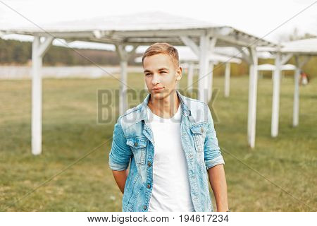 Young Man In A Stylish Denim Jacket And A White T-shirt Is Walking Outdoors On A Spring Day