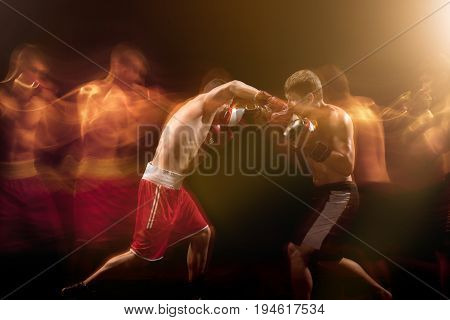 The two male athlete boxers punching with dramatic edgy lighting in a dark studio. Image made with stroboscope