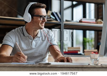 Comfy atmosphere. Diligent ambitious easy going man perusing some information and making some notes while having a productive day in the office