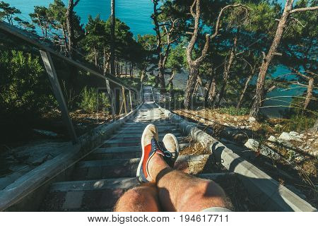 Hiker Man Sitting On Steps Of Stairs Coast Above Sea View Of Legs. Point Of View Shot