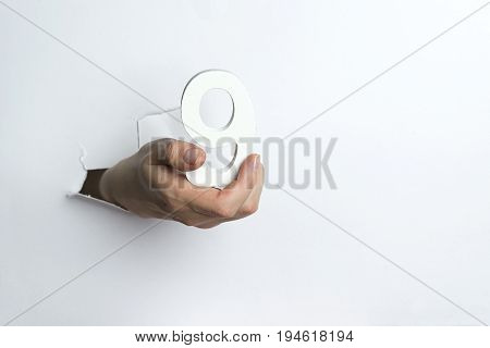 Woman's Hand Holding The Number Nine White Background.