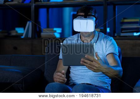 Setting up the gear. Attractive curious daring guy wearing special glasses and holding up his tablet while exploring virtual reality