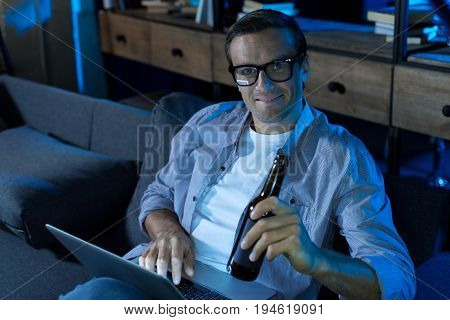 What can be better. Handsome vibrant lively guy relaxing on a couch in his living room and enjoying nice movie while sipping a drink from the bottle