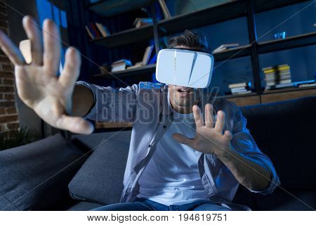 Gaming invention. Innovative ambitious active guy sitting on a couch and wearing special glasses while exploring virtual reality