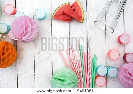Fresh melon with colorful accessories for a summer party decorated on white wood