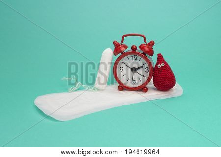 Red alarm clock smile crochet blood drop daily menstrual pad and tampon. Menstruation sanitary woman hygiene. Woman critical days gynecological menstruation cycle. Medical conception photo