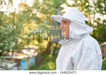 Profile portrait of a senior man in beekeeping suit posing outdoors copyspace beekeeper profession occupation hobby lifestyle farmer farming concept.