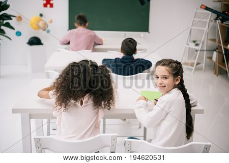 Back View Of Pupils Sitting At Desks And Cute Schoolgirl Smiling At Camera In Classroom