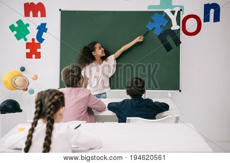 Smiling African American Schoolgirl Pointing At Chalkboard While Classmates Studying At Desks