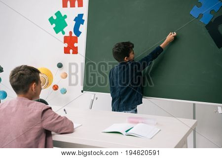 Back view of schoolboy writing on chalkboard while classmate studying at desk