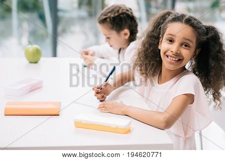 Adorable African American Schoolgirl Smiling At Camera While Classmate Studying Behind In Class