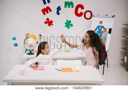 Cheerful multiethnic schoolgirls giving high five in classroom
