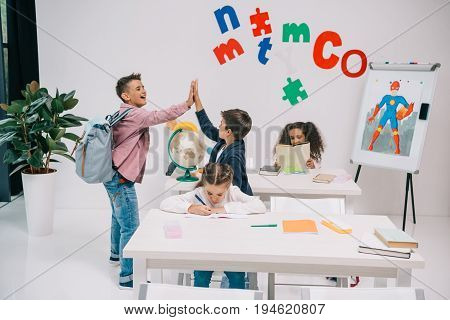 Cheerful schoolboys giving high five while schoolgirls studying in classroom