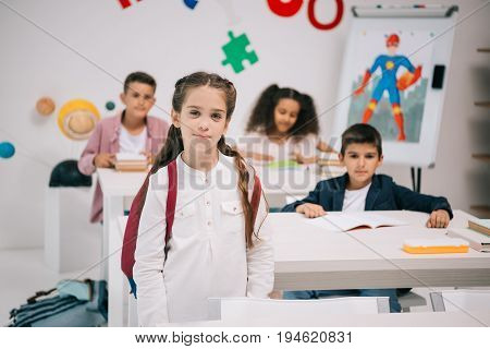Cute Smiling Schoolgirl With Multiethnic Classmates Looking At Camera In Classroom