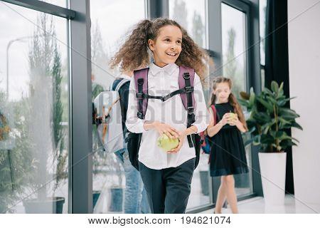 Smiling African American Schoolgirl Holding Apple And Looking Away In School Hallway