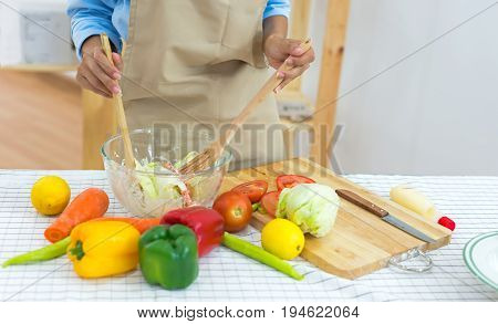 Woman hand cook make mix vegetables salad on kitchen for diet. Healthy Concept.