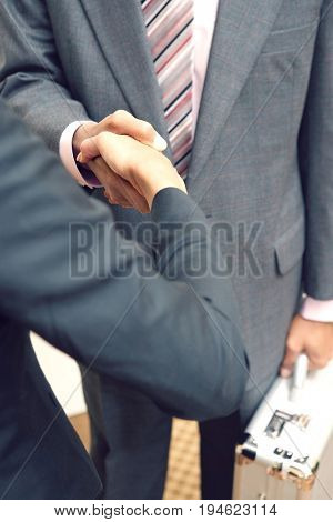 Business man and woman shaking hands, mid section