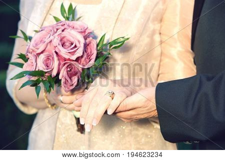 Middle-aged couple holding hands, woman holding bouquet, mid-section, close-up of hands