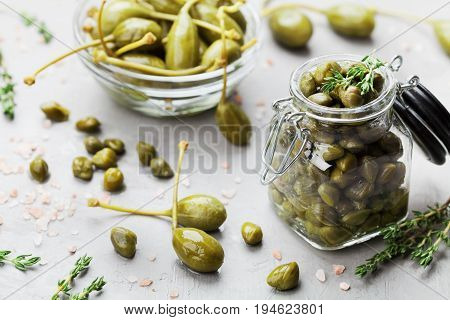 Mixed capers in jar and bowl on gray kitchen background.