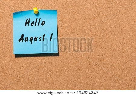 Hello August on blue sticker pinned to cork noticeboard with empty space for text.