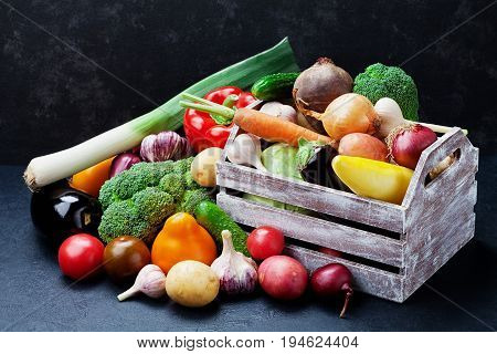 Wooden box with autumn harvest farm vegetables and root crops on black kitchen table. Healthy and organic food.