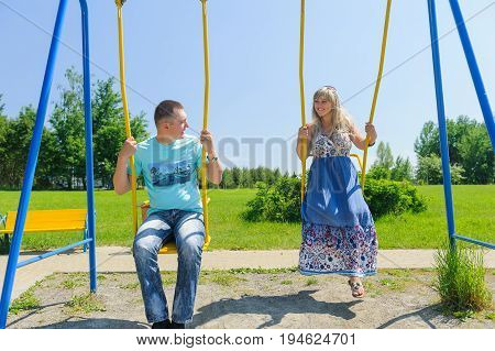 Couple having fun on the swing. Amorous couple on romantic date on swings outdoor. Love, relationship, family and people concept - smiling couple hugging in summer park