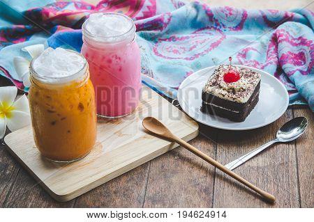 thai tea milkshake and pink milkshake beverage thailand style and cake chocolate dessert on wood table