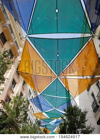 Yellow green blue fabric roof decoration on a street for summer in Madrid Spain.