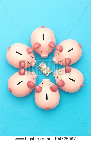 Piggy banks surrounding roll of dollar bills, blue background, view from above