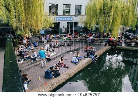 UK London - 08 April 2015: The Camden Market in London England. People are sitting on the asphalt
