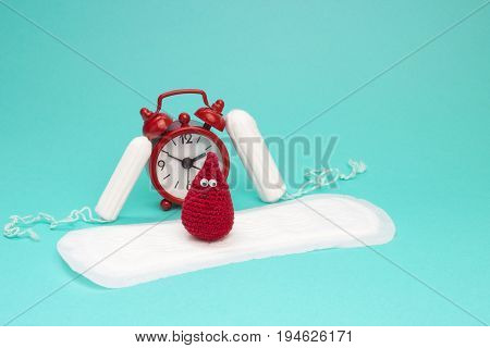 Red alarm clock dreamy smile crochet blood drop daily menstrual pad and tampons. Menstruation sanitary woman hygiene. Woman critical days gynecological menstruation cycle. Medical conception photo