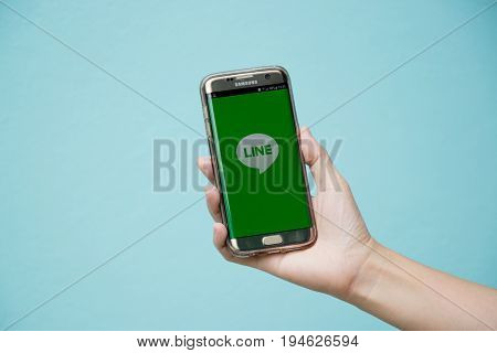 Bangkok Thailand July 8 2017 : Woman held android smart phone Samsung galaxy S7 Edge with line application screen on blue concrete background.
