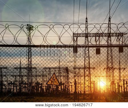Impression network at transformer station in sunrise high voltage up to yellow sky take with yellow tone horizontal frame