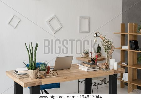 Office Table With Laptop, Books, Candles And Office Supplies