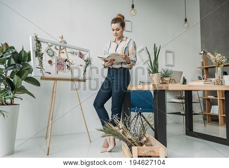 Confident Attractive Female Florist Holding Book And Standing At Board In Office