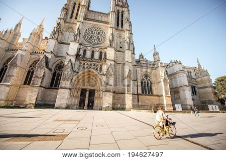 BORDEAUX, FRANCE - May 24, 2017: Morning view on the saint Pierre cathedral facade with woman ride the bicycle in Bordeaux city, France