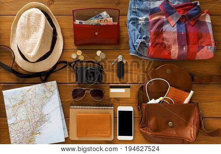 Vacation travel planning, tourist essentials set top view. Preparing for trip, flat lay of traveller baggage, blank smartphone screen, copy space