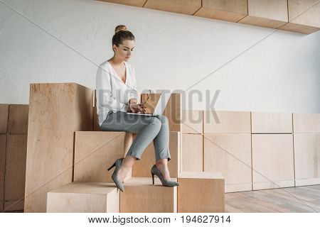 Attractive Fashionable Businesswoman Working With Laptop While Sitting On Wooden Cubes